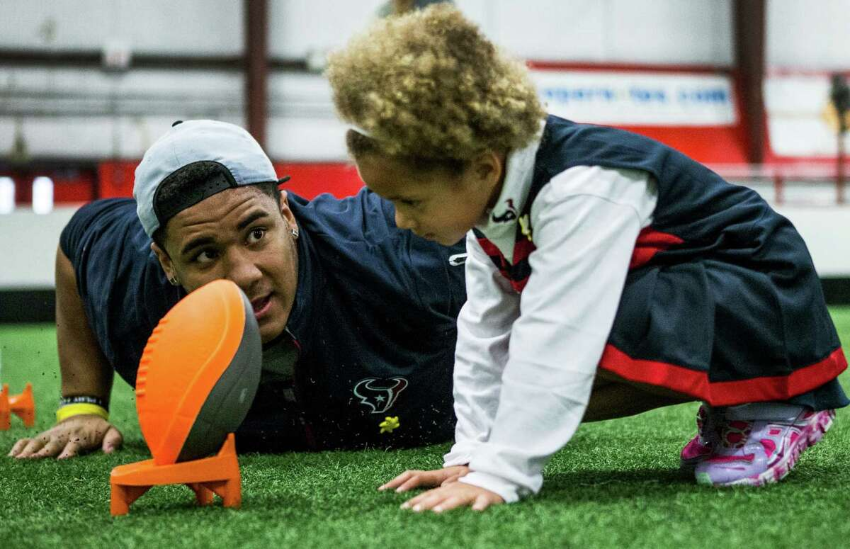 Houston Texans defensive tackle Christian Covington helps Shelby Jackson, 4, line up a kick during a football training camp for the Sunshine Kids at Southwest Indoor Soccer on Wednesday, Feb. 17, 2016, in Stafford. More than 100 young cancer patients and their siblings participated in the event, learning and playing football skills games.