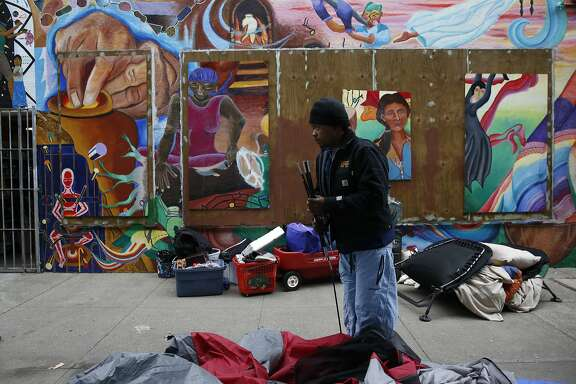Archie Williams packs up a tent after he and others who have been living along the sidewalk said that the police told them to move from their spot along Division Street Feb. 17, 2016 in San Francisco, Calif.