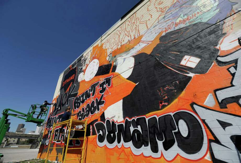 Mario E. Figueroa, Jr., left, better known as Gonzo247 and Jojo Villarreal, right, paint a Dynamo graffiti art mural featuring the new black jersey at the corner of Leeland and Chartres Streets Wednesday, Feb. 17, 2016, in Houston. Photo: Melissa Phillip, Houston Chronicle / © 2016 Houston Chronicle
