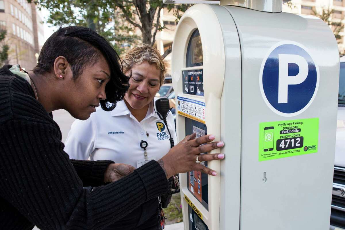 Tyra Brown uses one of the city's new parking meters as Olga Valdez, parking compliance officer, stands by on Tuesday in Houston.