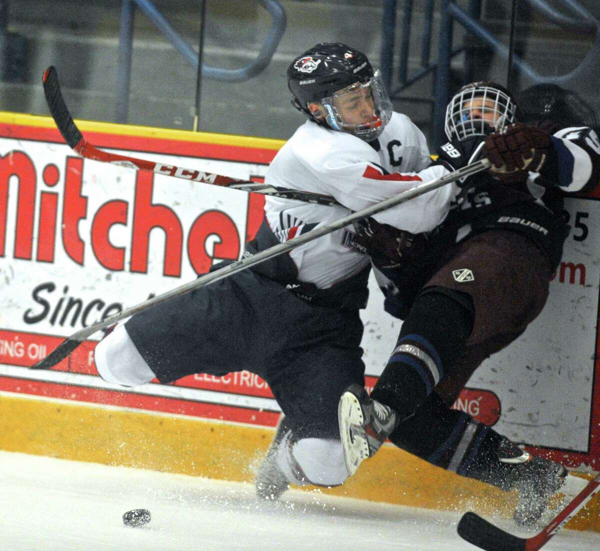 NFI's Joseph Lane (4) checks BBD's Tanner Trew (15) into the boards during the boys high school ice hockey game between Brookfield-Bethel-Danbury and New Fairfield-Immaculate on Wednesday, February 17, 2016, at the Danbury Ice Arena, in Danbury, Conn.