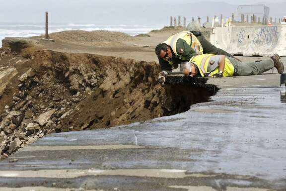 CJ Maes (left) and Jim Fusscas of the National Park Service look at the eroding cliff face after a large chunk of asphalt recently fell onto the beach below at a parking lot south of Ocean Beach in San Francisco, California, on Wednesday, Feb. 17, 2016.