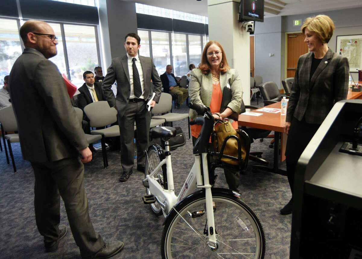 Douglas Melnick, left, the city's chief sustainability officer, and JD Simpson, second from right, executive director of the nonprofit San Antonio Bike Share, show the new B-Cycle 2.0 to City Manager Sheryl Sculley before a meeting with the San Antonio City Council on Wednesday. B-Cycle, the city's bike sharing program, is adding three new stations at The Pearl, San Antonio College and the DoSeum. It also plans to introduce 50 of the newer, sleeker bikes in April.