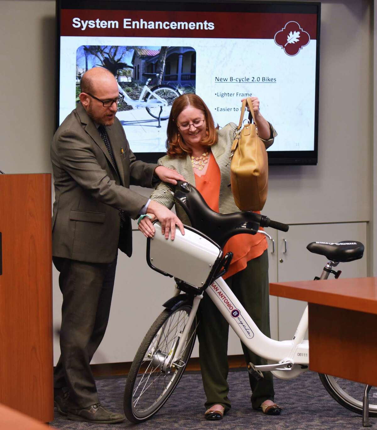 Douglas Melnick, left, the city's chief sustainability officer, and JD Simpson, executive director of the nonprofit San Antonio Bike Share, display a new B-Cycle 2.0 during a meeting of the San Antonio City Council on Wednesday. B-Cycle, the city's bike sharing program, plans to introduce 50 of the newer, sleeker bikes in April, and more later.