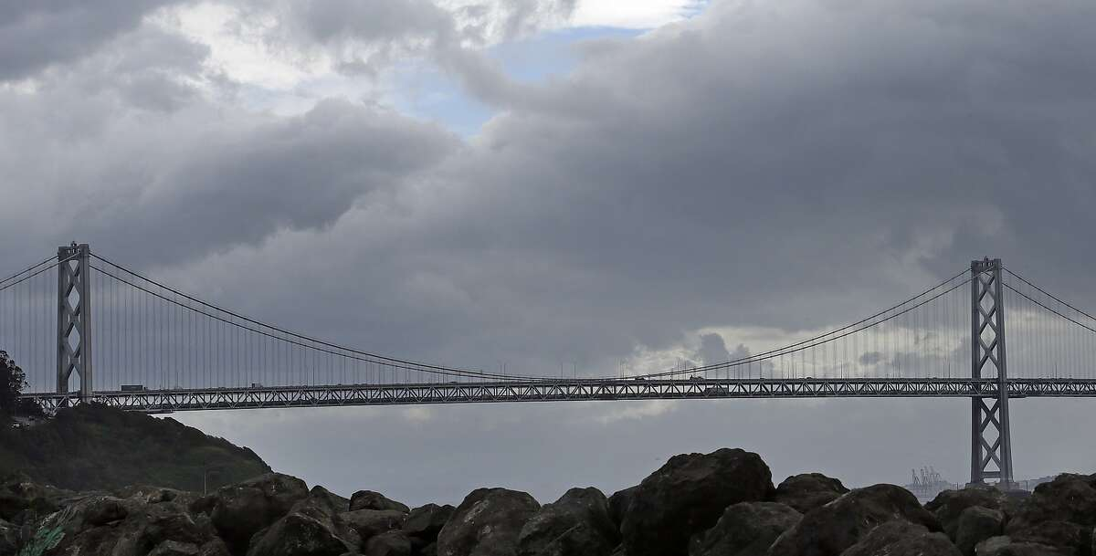 Storm clouds pass over the Oakland-San Francisco Bay bridge Wednesday, Feb. 17, 2016. After three days of record-breaking heat, a cold front from Oregon brought high winds and rain to Northern California, Wednesday with strong gusts in the San Francisco Bay Area. (AP Photo/Ben Margot)