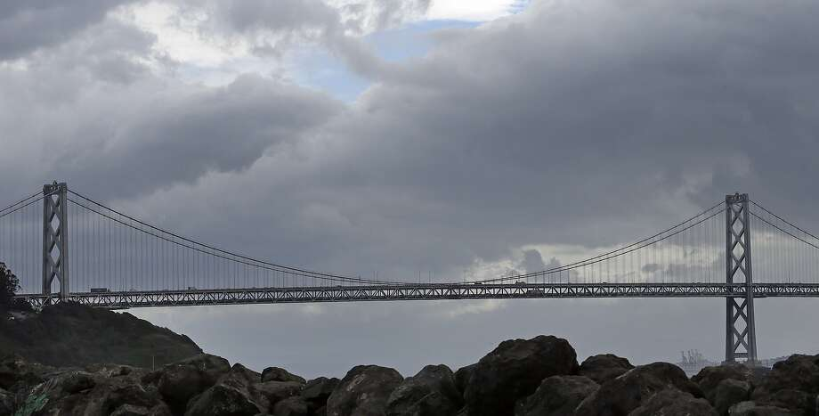 Storm clouds pass over the Oakland-San Francisco Bay bridge Wednesday, Feb. 17, 2016. National Weather Service says scant rain fell in February, leaving a lot of catching up to do in March to put a dent in the drought. Photo: Ben Margot, Associated Press