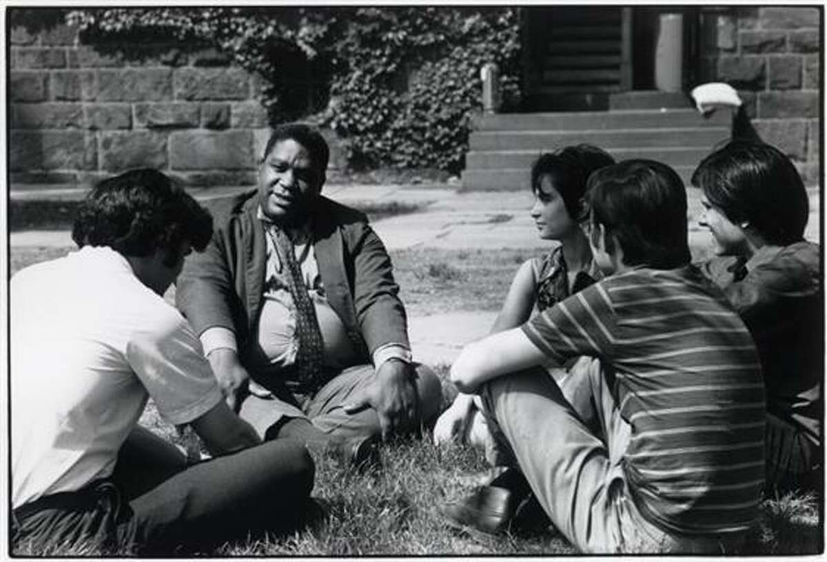 Students and professor holding a class outside.