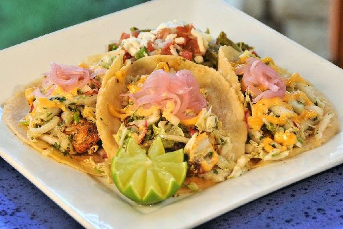 At La Fonda on Main, fish tacos are wrapped in housemade corn tortillas, dotted with some chipotle mayo and topped with a bit of napa cabbage slaw with a side of nopalito salad.