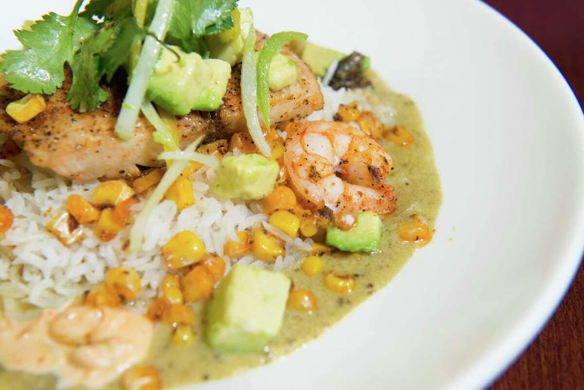 Adobo Seafood combines mahi mahi and shrimp with roasted corn kernels and sauteed sweet peppers and onions, served on basmati rice with a poblano cream sauce and chipotle aioli.