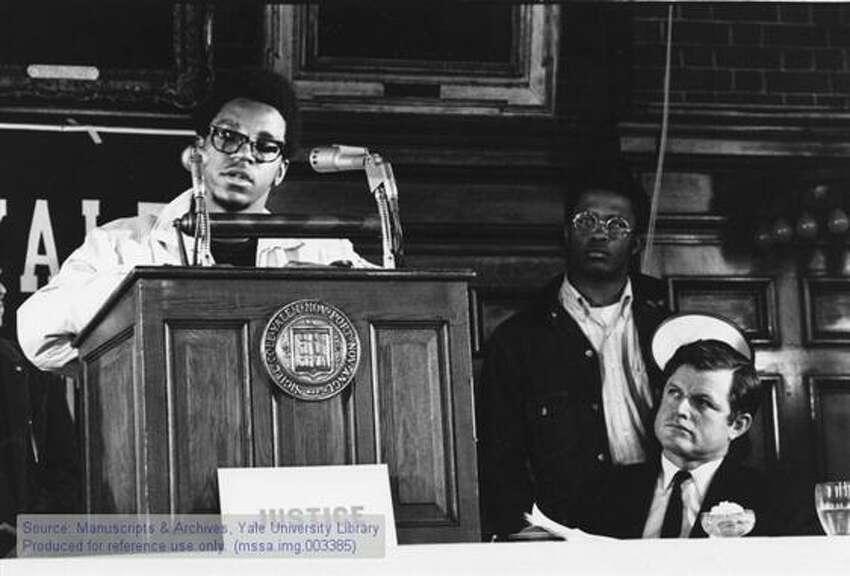 Ralph Dawson speaking with Senator Edward Kennedy, Democrat of Massachusetts, and undergraduate Kurt Schmoke standing behind Kennedy.