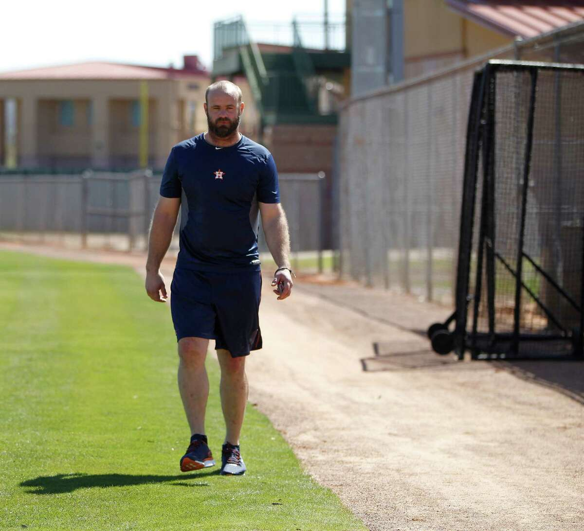 Houston Astros Evan Gattis walks around a field as he worked with assistant athletic trainer, James Ready, during report day for Houston Astros pitchers and catchers at their Osceola County facility, in Kissmmee, FL, Thursday, Feb. 18, 2016.