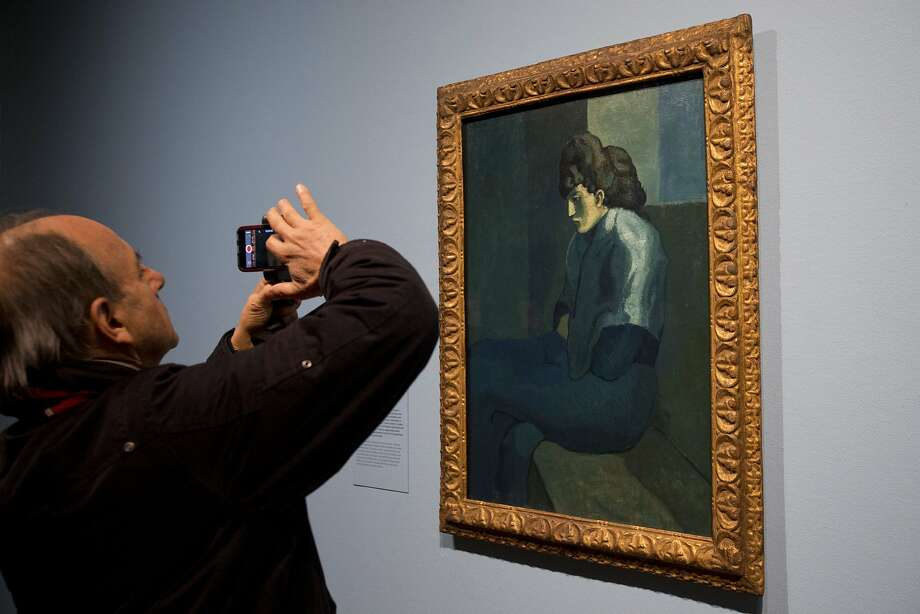 A man takes a picture of Pablo Picasso's painting