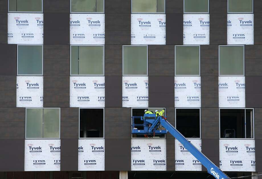 Workers install window panes on a building under construction at a technology campus across from the BART station in San Leandro. Photo: Paul Chinn, The Chronicle