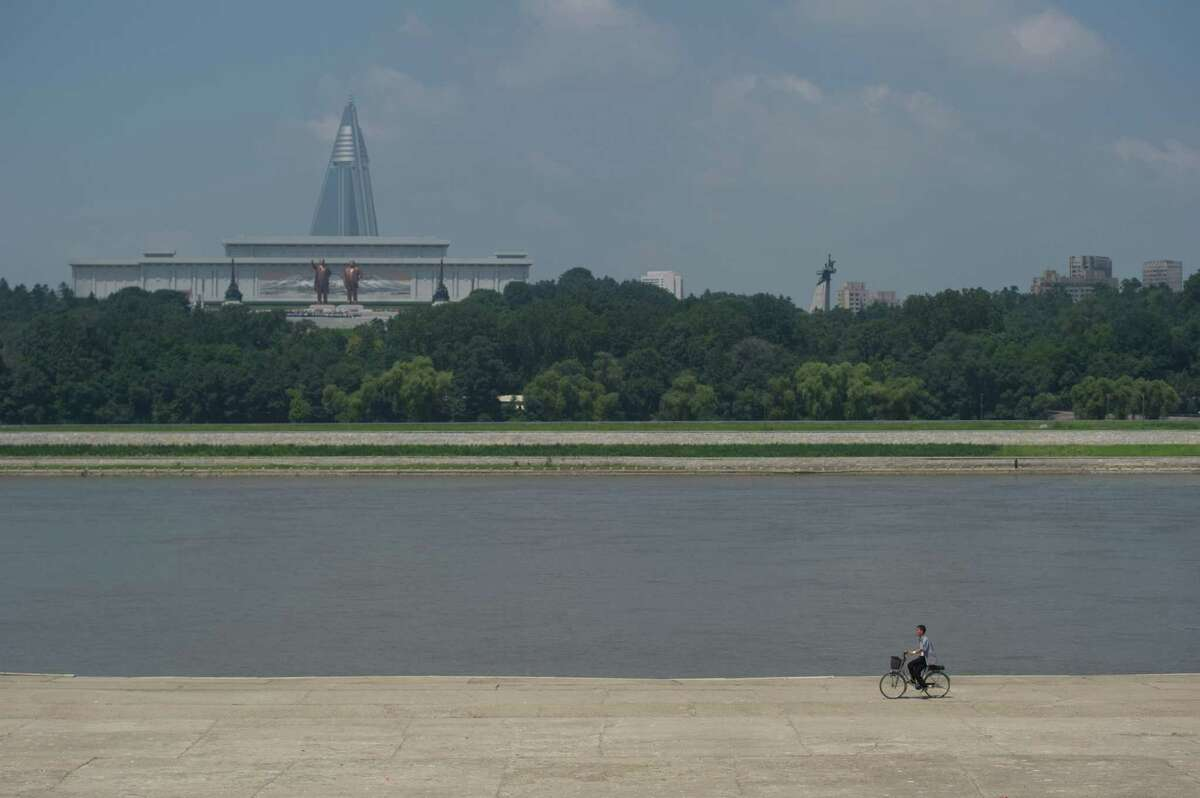 A cyclist (bottom R) rides along a bank of the Taedong river in front of a view of the Ryugyong Hotel (back L) behind statues of late North Korean leaders Kim Il-Sung (L) and Kim Jong-Il (R) in Pyongyang on July 26, 2013. North Korea is preparing to mark the 60th anniversary of the end of the Korean War which ran from 1950 to 1953, with a series of performances, festivals, and cultural events culminating with a large military parade. AFP PHOTO / Ed Jones