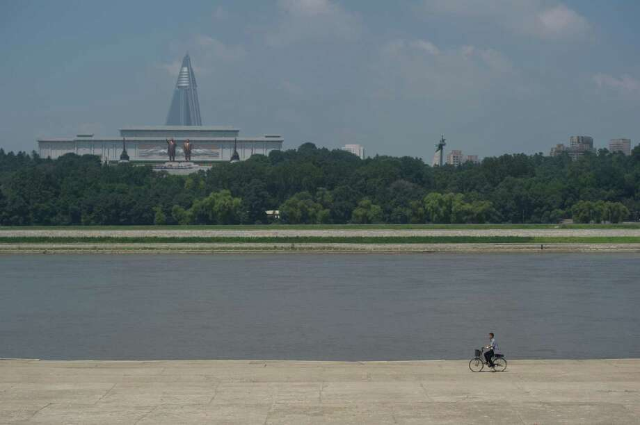 A cyclist (bottom R) rides along a bank of the Taedong river in front of a view of the Ryugyong Hotel (back L) behind statues of late North Korean leaders Kim Il-Sung (L) and Kim Jong-Il (R) in Pyongyang on July 26, 2013. North Korea is preparing to mark the 60th anniversary of the end of the Korean War which ran from 1950 to 1953, with a series of performances, festivals, and cultural events culminating with a large military parade. AFP PHOTO / Ed Jones Photo: ED JONES, Getty Images / 2013 AFP