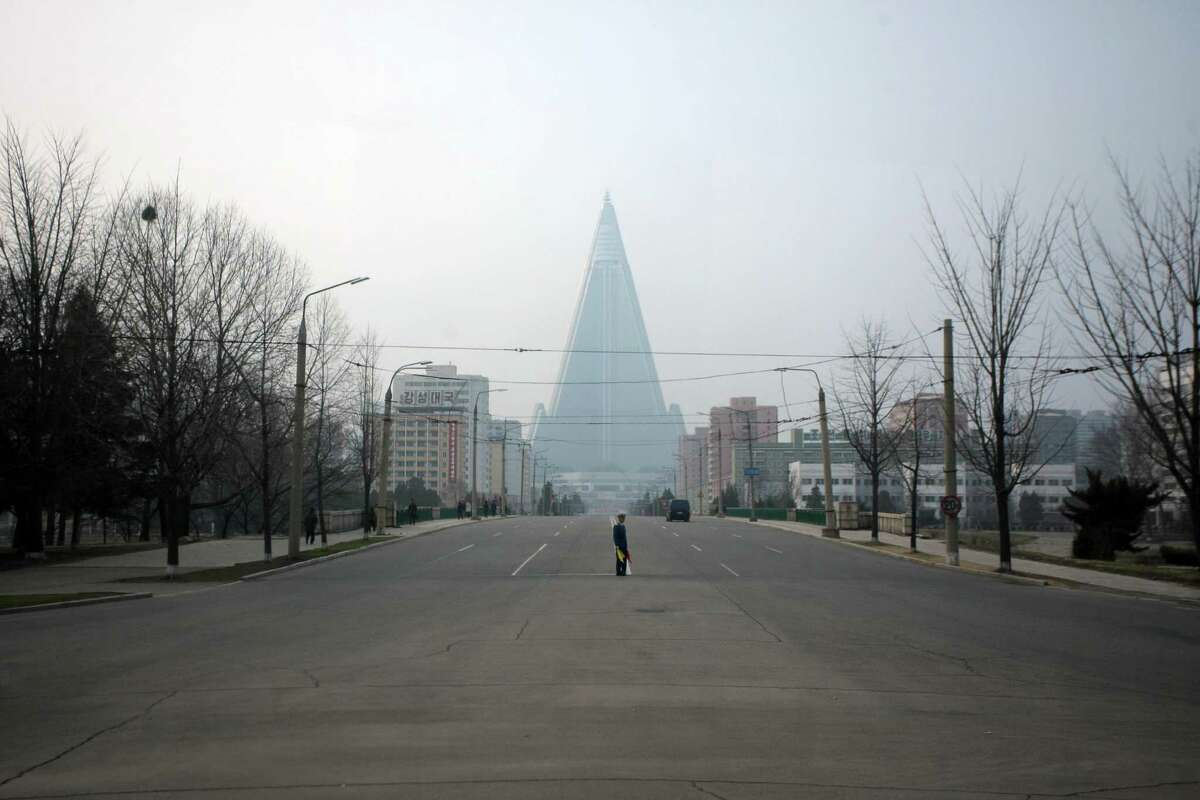 A traffic warden is seen from the window of a bus as he stands on an empty street before the Ryugyong Hotel in Pyongyang on April 12, 2012. North Korea's five-day window to launch a rocket opened with Asian countries on alert, as Washington told G8 world powers that the communist state was in flagrant violation of a UN ban. AFP PHOTO / Ed Jones