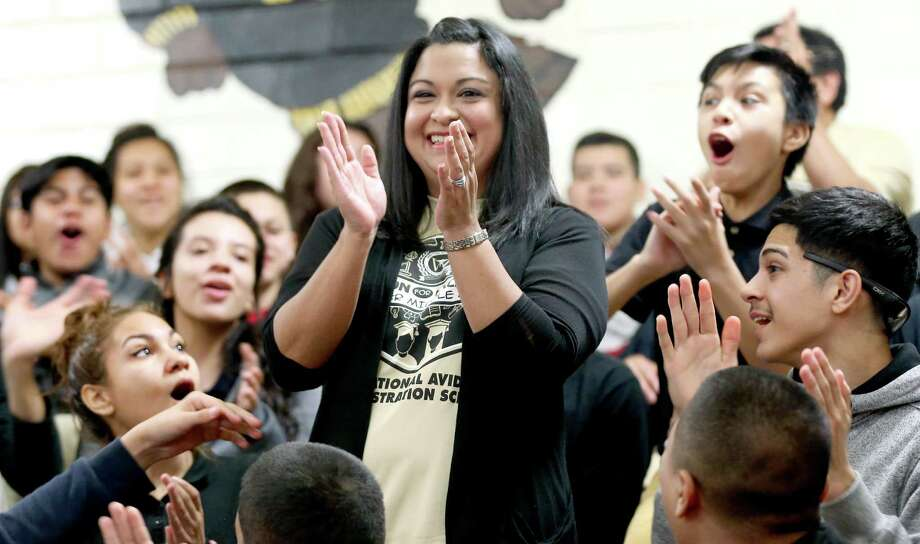 Whittier Middle School math teacher Laura Servin stands Thursday morning Feb. 18, 2016 as her students react to her receiving the Milken Education Award. The only teacher in Texas to receive the award this year, Servin receives a $25,000 award she is allowed to spend as she wants, according to the Milken Family Foundation which administers the prize. Photo: William Luther, Staff / San Antonio Express-News / © 2016 San Antonio Express-News