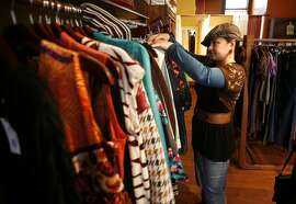 """Clothing for sale at the Issosf (""""Is So San Francisco"""") store at 3789 24th St. in San Francisco, Calif., comes from local second-hand sources. Sales associate Josie Lazo arranges displays at the store on Tuesday, Nov. 25, 2008."""