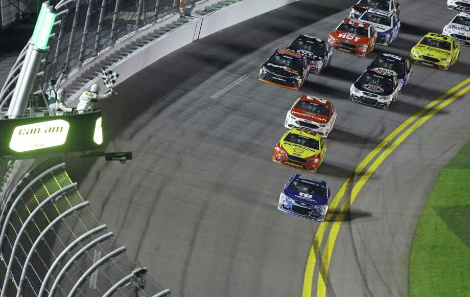 Dale Earnhardt Jr, front, prepares to take the checkered flag to win the first of two qualifying races for Sunday's NASCAR Daytona 500 Sprint Cup series auto race at Daytona International Speedway in Daytona Beach, Fla., Thursday, Feb. 18, 2016. Photo: David Graham, AP / FR46423 AP