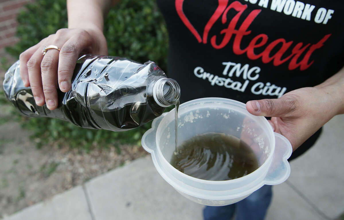 Mary Jane Surita pours from the bottle of discolored water she drew from her bathroom faucet as Crystal City residents deal with dark, polluted tap water on February 17, 2016.