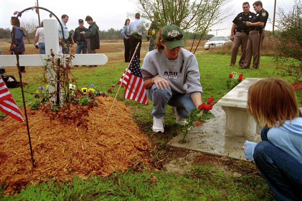 Cathy Hill and her daughter Whitney, then 8, visited in 2002 the grave of their husband and father, Sheriff's Deputy Barrett T. Hill. Cathy Hill now faces charges that she embezzled $108,000 from the Harris County deputies' union.