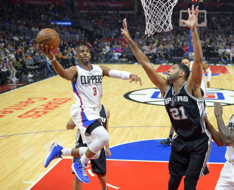 Los Angeles Clippers guard Chris Paul, left, shoots as San Antonio Spurs center Tim Duncan defends during the first half of an NBA basketball game Thursday, Feb. 18, 2016, in Los Angeles. (AP Photo/Mark J. Terrill)