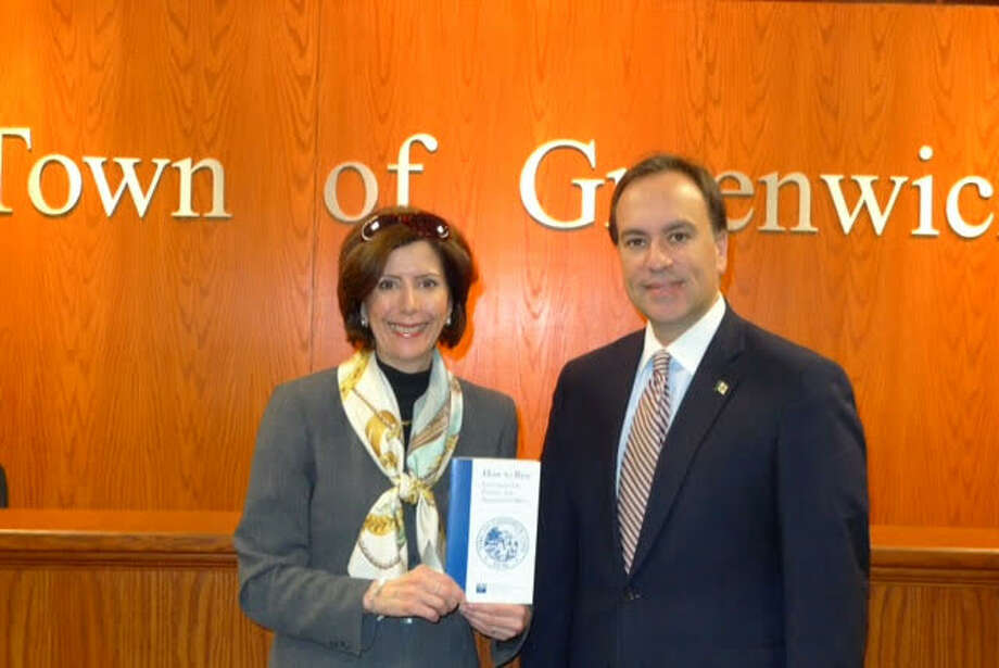 Deirdre Kamlani, who was in charge of the updates, presents First Selectman Peter Tesei with the new version of the guide which shows how to run for office in town. Photo: / Contributed Photo