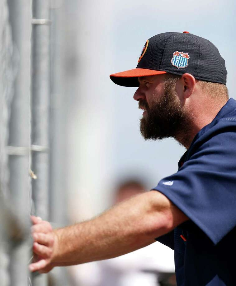 Houston Astros outfielder Evan Gattis watches pitchers throw off the ten-pack during the first
