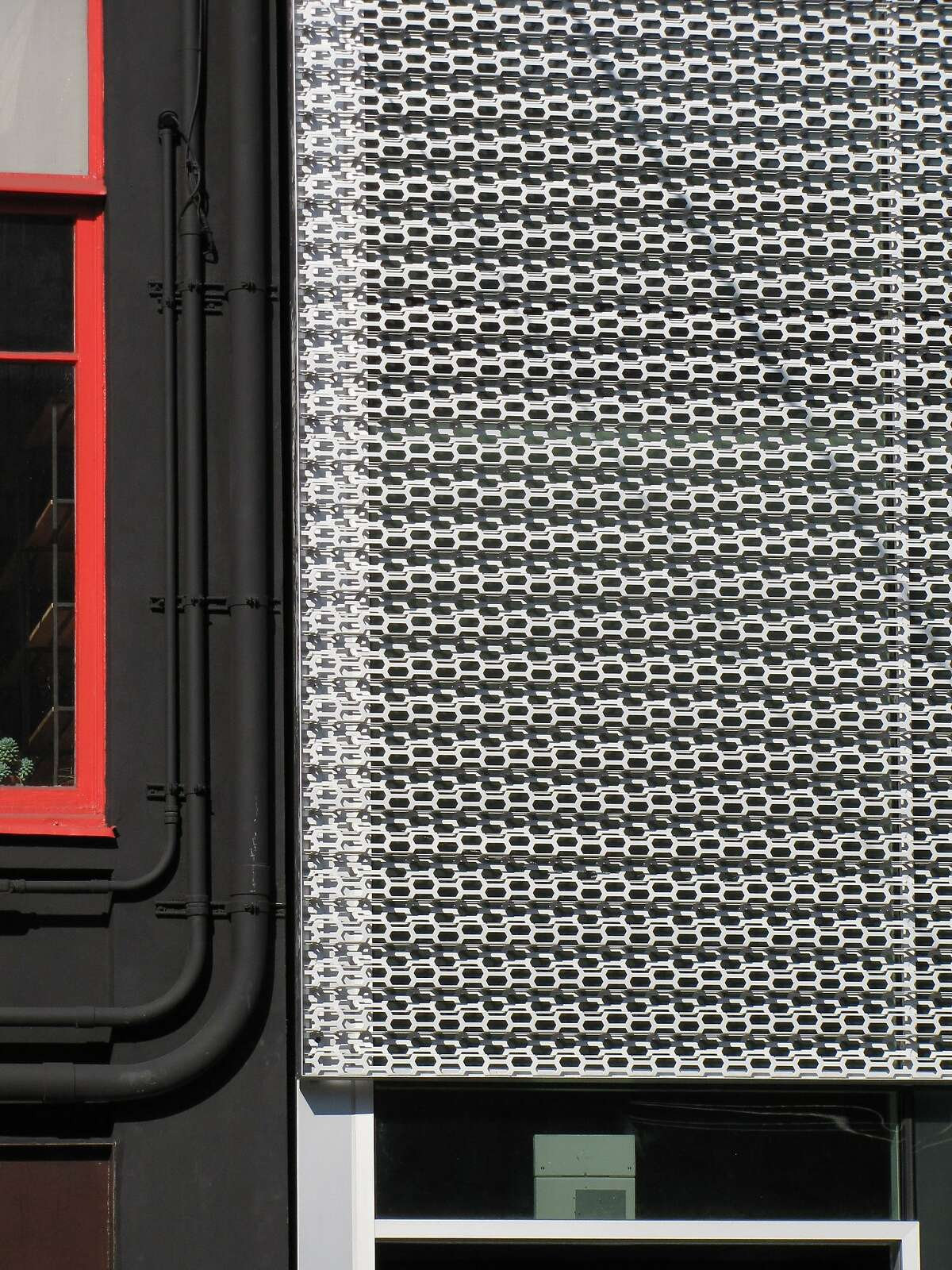 The new commercial building at 482 Bryant St. is set apart from its neighbors by an unusual perforated skin that covers everything above the entrance