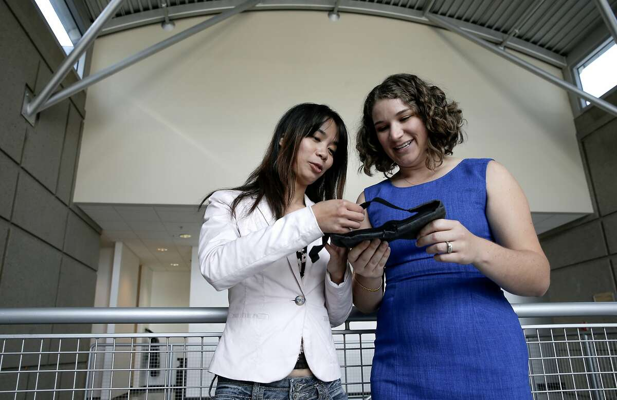 LumosTech COO Biquan Luo (left) and CEO Vanessa Burns examine a mask designed to combat jet lag.