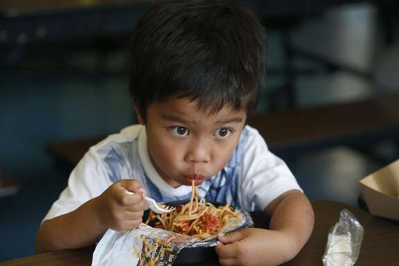 Kindergartner Colin Wolfert eats a spaghetti lunch from a recyclable plastic tray at Commodore Sloat School in San Francisco, Calif. on Friday, Feb. 19, 2016. Schools across the city have been asked not to place recyclable trays in recycle bins because of excess food particles clinging to them.