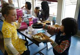 Flora Zhang (right) hands a recyclable plastic lunch tray to her kindergarten classmate Olivia Quigley at Commodore Sloat School in San Francisco, Calif. on Friday, Feb. 19, 2016. Schools across the city have been asked not to place recyclable trays in recycle bins because of excess food particles clinging to them.
