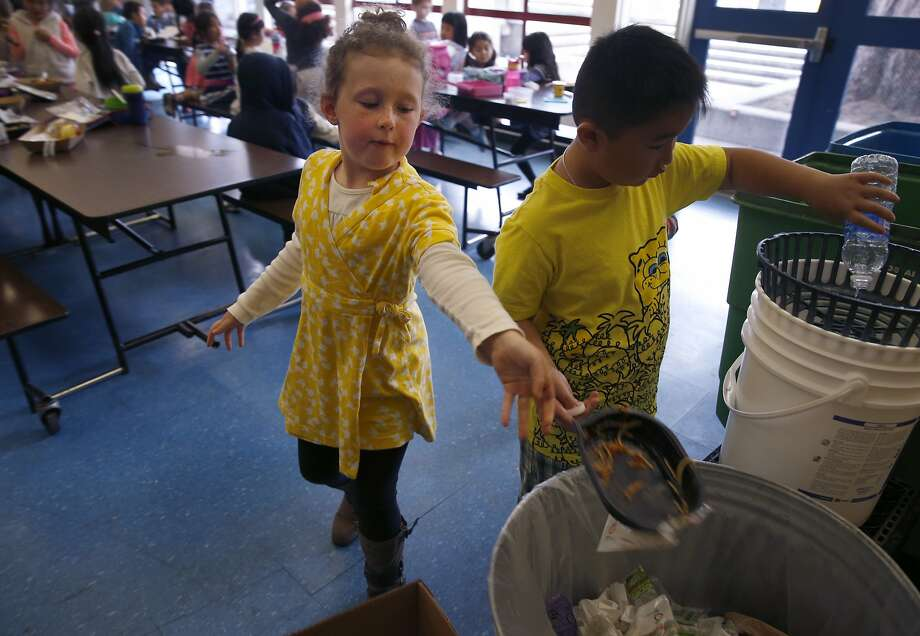 Kindergartner Olivia Quigley tosses a recyclable lunch tray into a trash can at Commodore Sloat School in San Francisco, Calif. on Friday, Feb. 19, 2016. Schools across the city have been asked not to place recyclable trays in recycle bins because of excess food particles clinging to them. Photo: Paul Chinn, The Chronicle