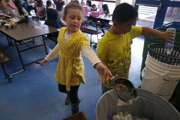Kindergartner Olivia Quigley tosses a recyclable lunch tray into a trash can at Commodore Sloat School in San Francisco, Calif. on Friday, Feb. 19, 2016. Schools across the city have been asked not to place recyclable trays in recycle bins because of excess food particles clinging to them.