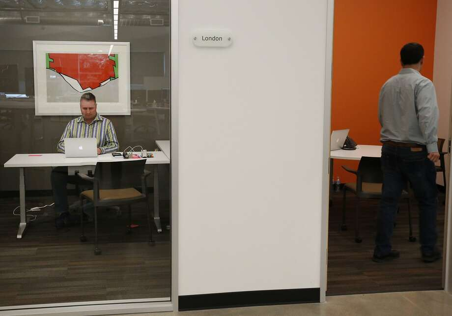 Tim Wenzel, head of talent acquisition, works in his office (left) at Menlo Park's Globality. Photo: Leah Millis, The Chronicle