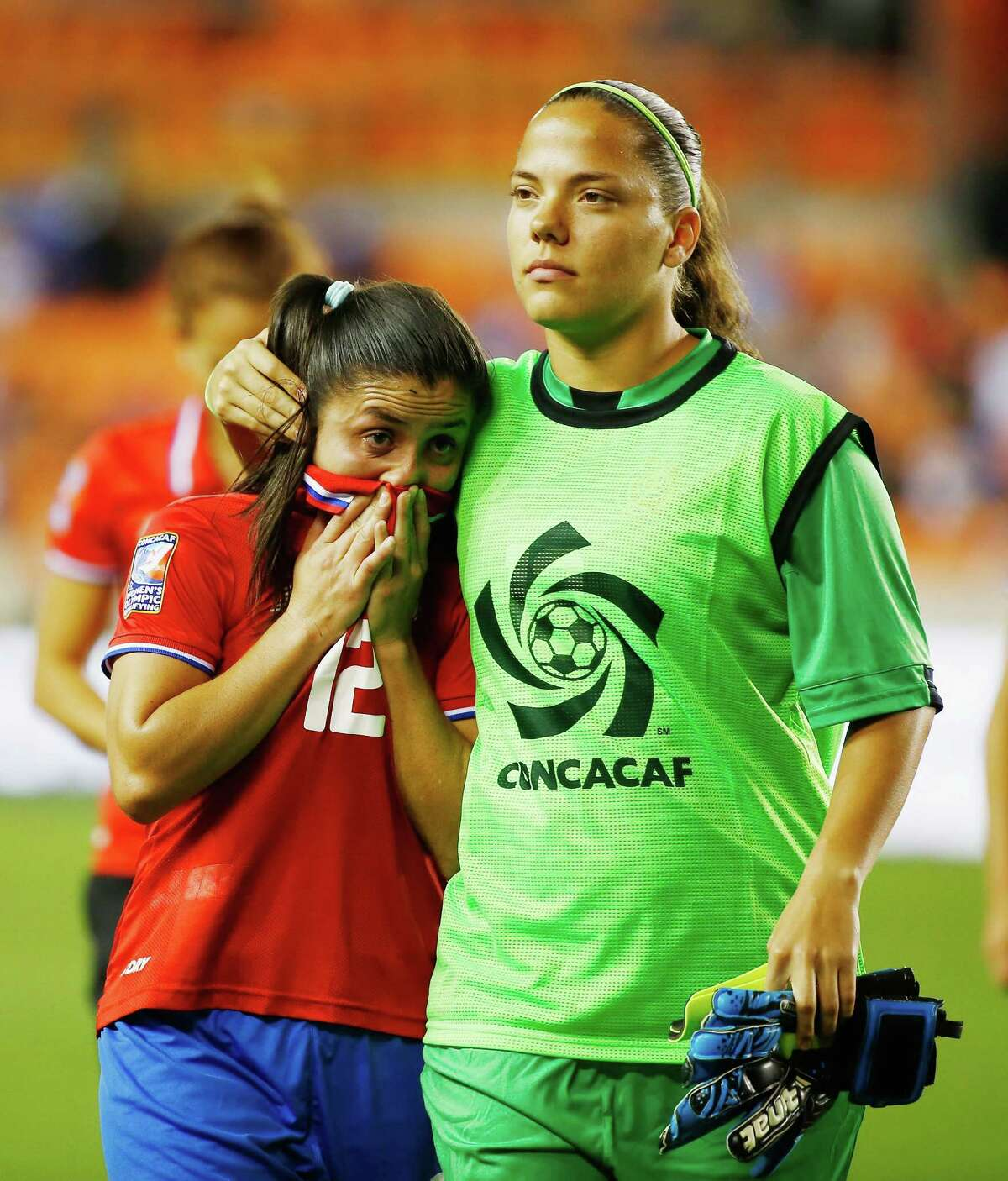 HOUSTON, TX - FEBRUARY 19: Lixy Rodriguez #12 and Yalitza Sanchez #13 of Costa Rica walk off the field after Costa Rica lost to Canada 3-1 during the Semifinal of the 2016 CONCACAF Women's Olympic Qualifying at BBVA Compass Stadium on February 19, 2016 in Houston, Texas.