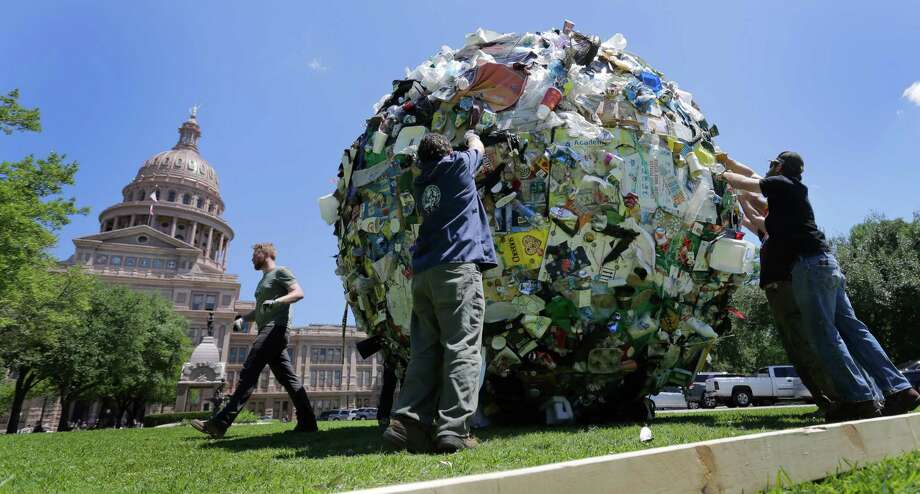 """Workers remove a large ball of trash from the lawn of the Texas Capitol, Wednesday, April 29, 2015, in Austin, Texas. The ball of trash was used as a prop by the Texas Department of Transportation to launch new announcements as part of the """"Don't mess with Texas"""" anti-litter campaign. Photo: Eric Gay, AP / AP"""