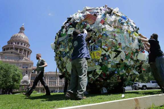 """Workers remove a large ball of trash from the lawn of the Texas Capitol, Wednesday, April 29, 2015, in Austin, Texas. The ball of trash was used as a prop by the Texas Department of Transportation to launch new announcements as part of the """"Don't mess with Texas"""" anti-litter campaign."""