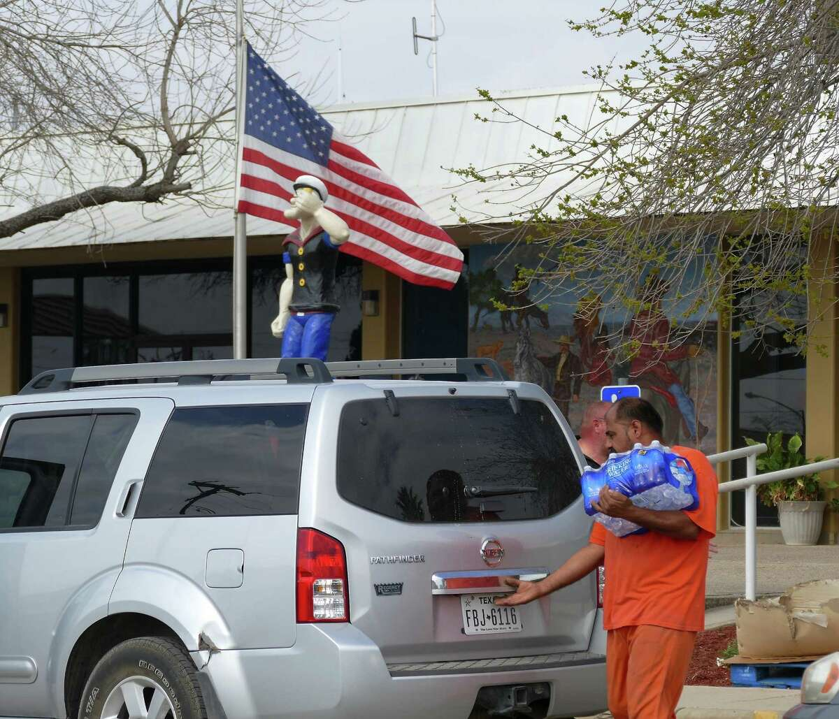 Jail inmates in Crystal City, Texas, help load donated water into vehicles on Friday, February 19, 2016. Tainted water began pouring out of faucets in the city this week during a system cleaning operation.