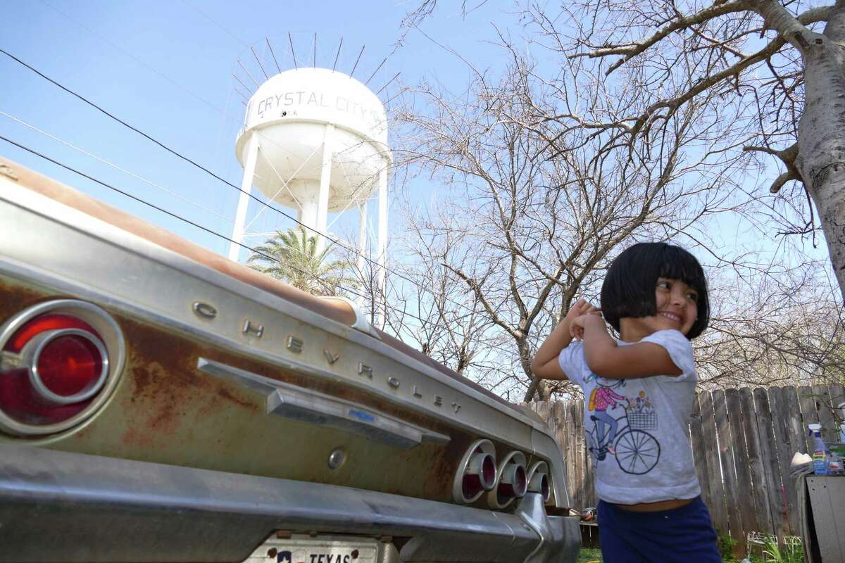 Crisyana Martinez plays in her family's yard by a water reservoir tower that is being cleaned in Crystal City, Texas, on Friday, February 19, 2016. Tainted water began pouring out of faucets in the city this week during a water system cleaning operation.