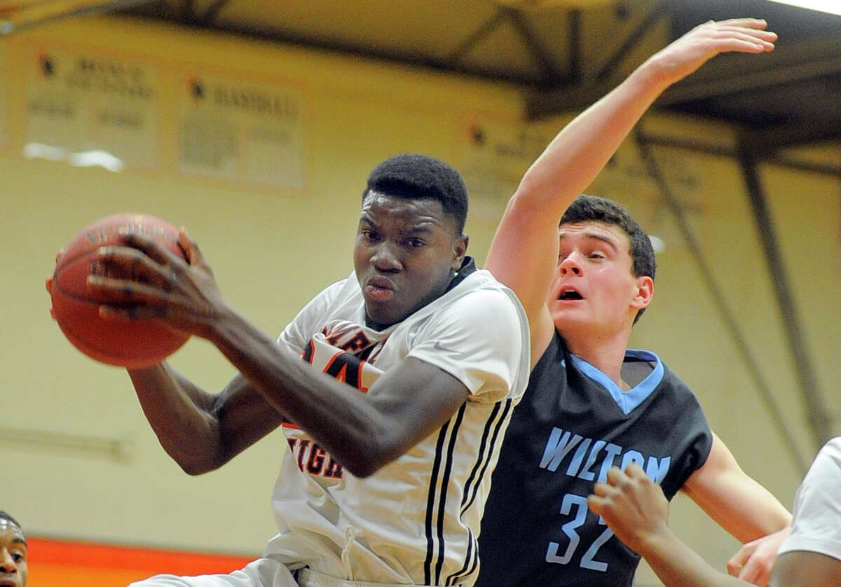 Stamford Nii Pobee (24) grabs a rebound from James Maloney (32) in the first half of an FCIAC basketball game at Stamford High School on Feb. 19, 2016. Stamford defeated Wilton 62-54.
