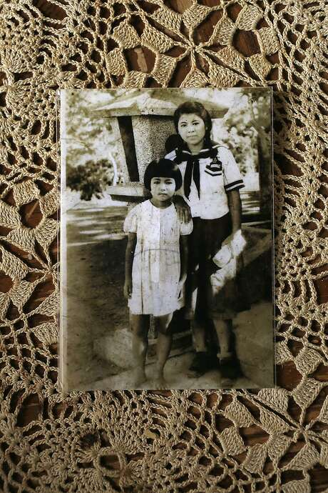Maria Miyagi Bartuff, 85 years old, shows a picture of cousin (left) and herself as a 16 year old child (right) in Okinawa at home in San Anselmo, California, on Friday, February 19, 2016.  Maria is a survivor of the sinking of the Japanese freighter tsushima maru in 1944 when she was 13 years old tells her story. Photo: Liz Hafalia, San Francisco Chronicle