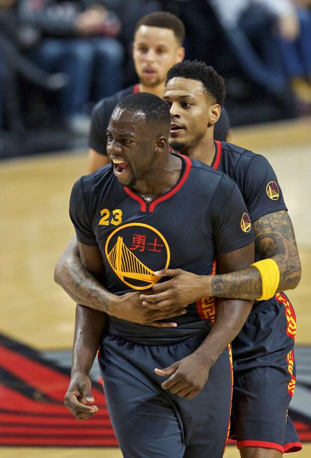 Warriors forward Draymond Green, left, reacts to a foul call and is held back by forward Brandon Rush, right, during the first half of a game against the Portland Trail Blazers on Friday. Photo: Craig Mitchelldyer, Associated Press
