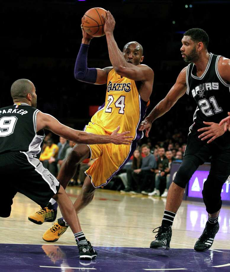 Los Angeles Lakers forward Kobe Bryant (24) drives the lane against San Antonio Spurs guard Tony Parker (9) and center Tim Duncan (21) during the first half of an NBA basketball game in Los Angeles, Friday, Feb. 19, 2016. (AP Photo/Alex Gallardo) Photo: Alex Gallardo, Associated Press / FR170211 AP