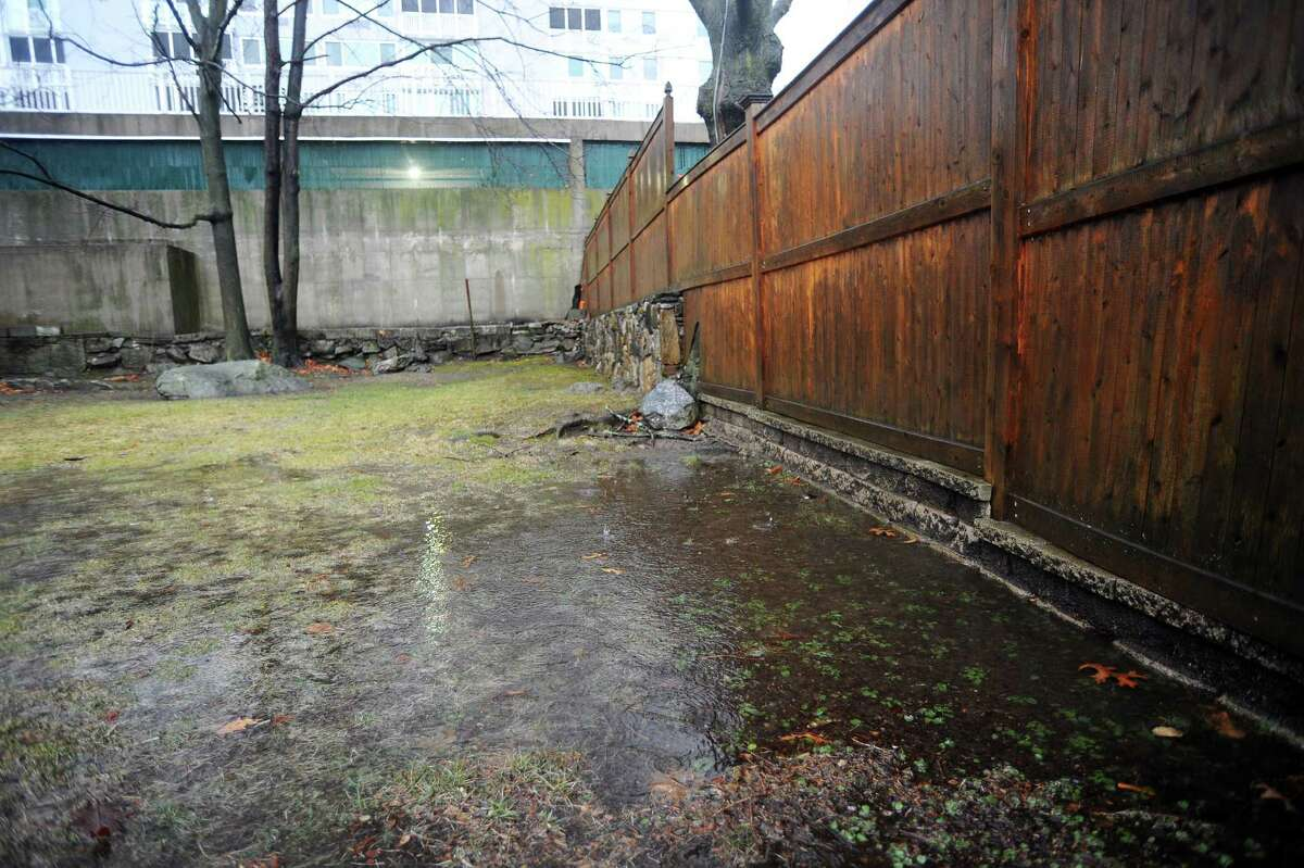 During heavy rain Stamford resident Stella Horton's Hillandale Ave. backyard consistently floods, creating small pools of water while soaking the rest of the yard. Ms. Horton blames the high rise apartment complex behind her, saying water runs off the parking garage and down the tall concrete wall onto her property. Photographed on Tuesday, Feb. 16, 2016.