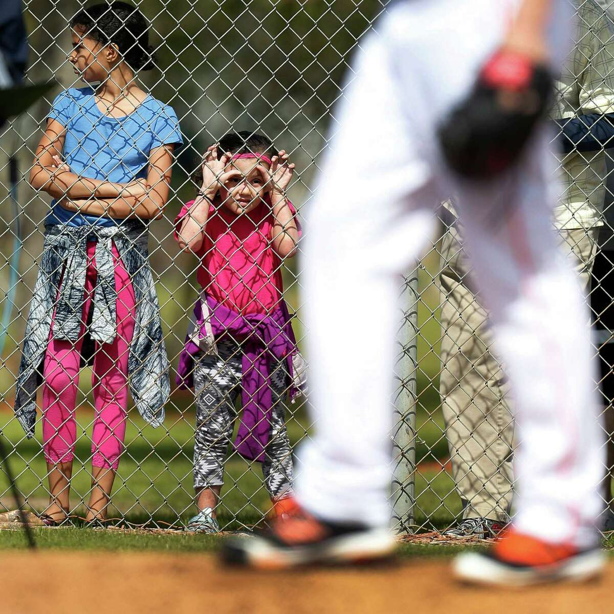 Kids watch Houston Astros pitcher Ken Giles pitch during spring training in Kissimmee, Florida, Saturday, Feb. 20, 2016.