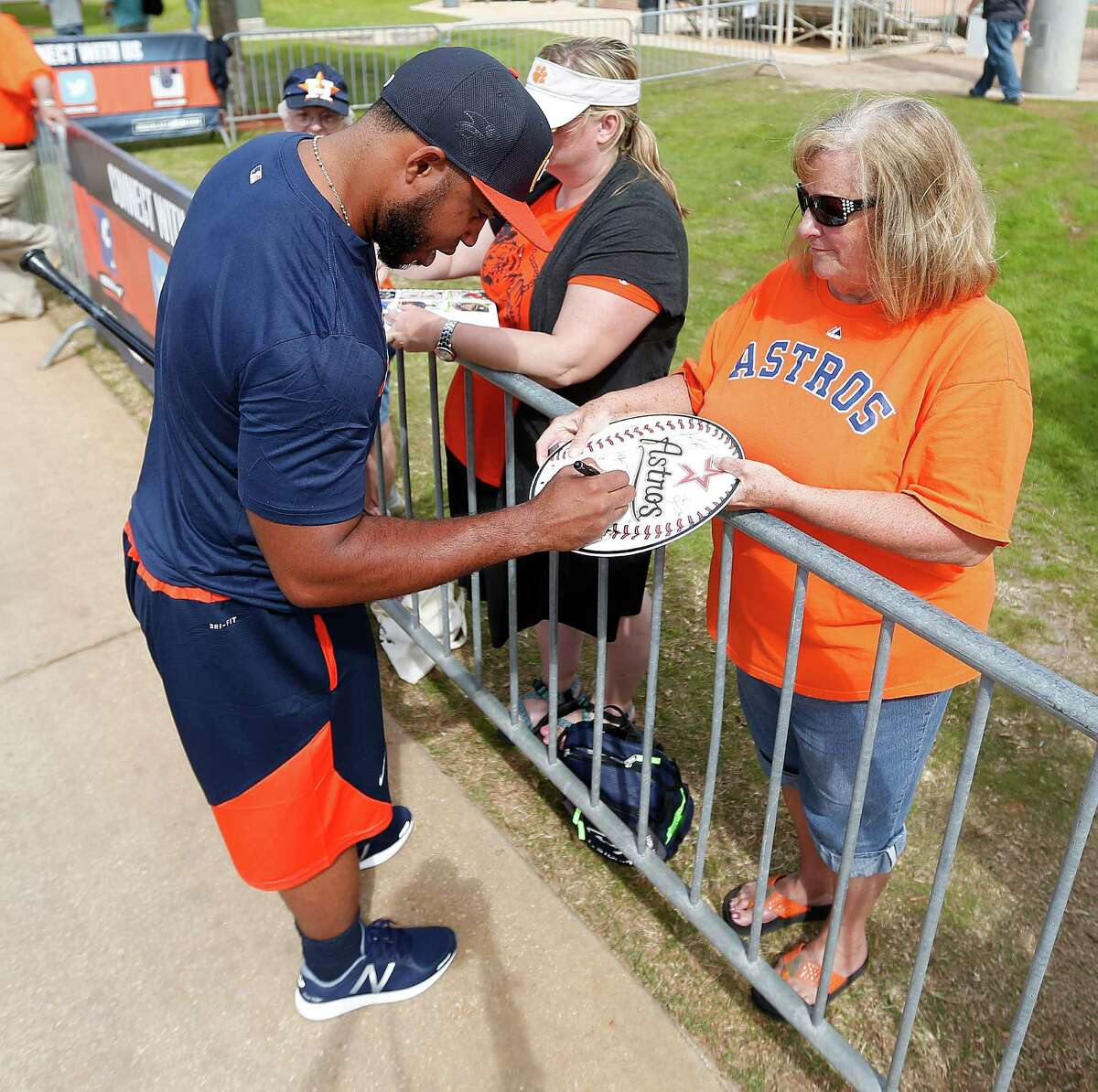 Houston Astros infielder Luis Valbuena signs an autograph for fan Carole Townsend as he walked back to the clubhouse after the batting cages during spring training in Kissimmee, Florida, Saturday, Feb. 20, 2016.