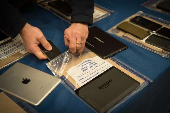 Encrypted smartphones held as evidence by the New York City Police Department are displayed at a news conference in New York, Feb. 18, 2016. Apple in the past has frequently helped the Justice Department unlock iPhones, but last fall, in connection with a routine drug case, it refused, foreshadowing a showdown with the Obama administration over the locked iPhone belonging to one of the San Bernardino shooting rampage suspects. (Bryan R. Smith/The New York Times)