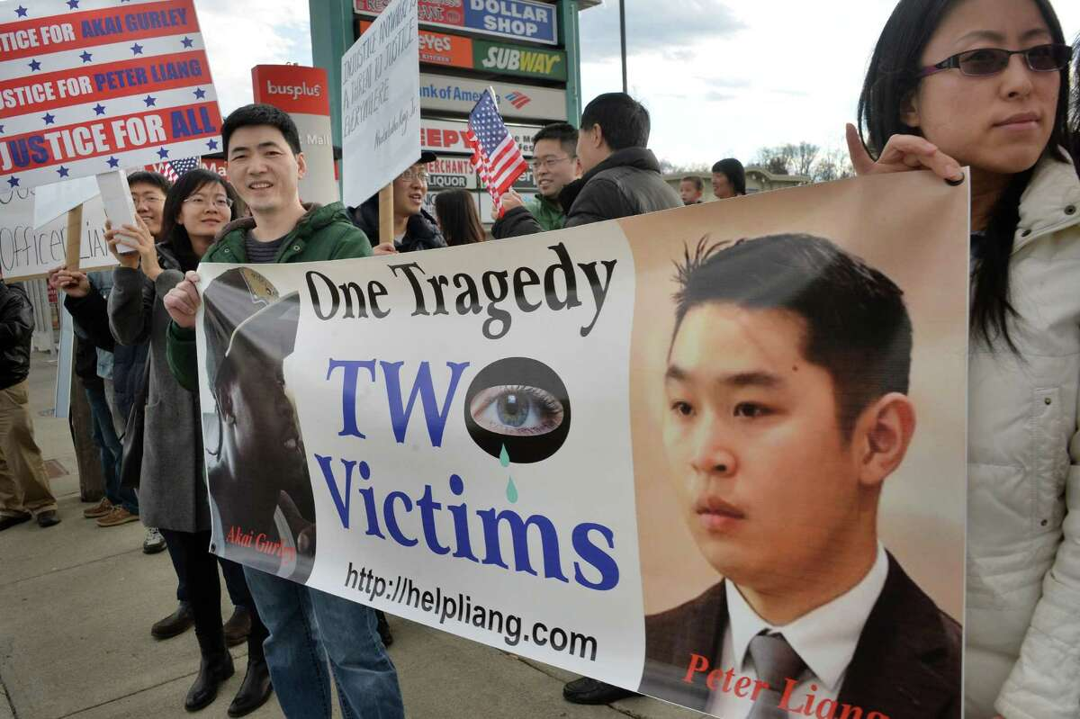 Members of the Capital Region's Asian community hold a protest on Central Ave. Saturday Feb. 20, 2016 in Albany, NY, in solidarity with similar events in 44 cities against the Feb. 11 conviction of former NYC cop Peter Liang. Liang was a rookie when he shot an killed an unarmed black man after he claims his service revolver went off by accident when he was responding to a call. (John Carl D'Annibale / Times Union)
