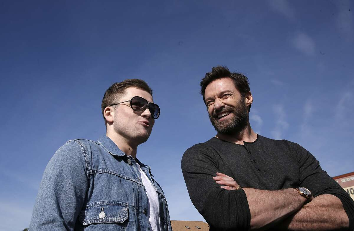 Taron Egerton, (left) and Hugh Jackman, co-stars of the new movie, Eddie The Eagle, on Sat. February 20, 2016, in Oakland, California. They joined NFL star Marshawn Lynch, during his youth football training program at Lynch's former high school Oakland Technical.